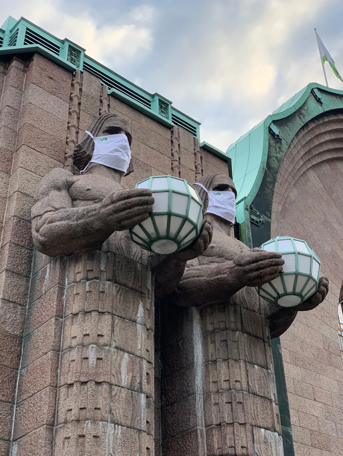 helsinki train station statues in masks